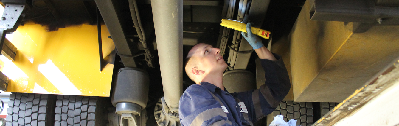 A mechanic inspecting the underside of a lorry